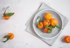 Tangerinen auf weißem hölzernem Hintergrund Graues Tupfengewebe Lizenzfreie Stockfotos