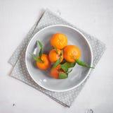 Tangerinen auf weißem hölzernem Hintergrund Graues Tupfengewebe Stockfotografie