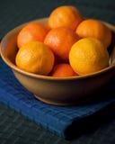 Tangerinen in der Schüssel auf blauem Placemat Stockbilder