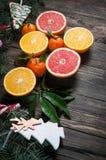 Tangerinen mit Blättern im Weihnachtsdekor mit Weihnachtsbaum, trockener Orange und Süßigkeiten über altem Holztisch Lizenzfreie Stockfotografie