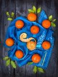 Tangerinen mit grünen Blättern auf blauem Tuch, dunkler hölzerner Hintergrund Stockbilder