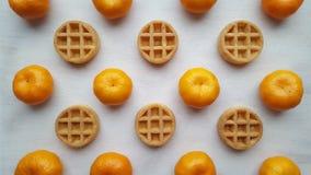 Tangerinen und Waffeln liegen auf einem hölzernen Behälter stockfotografie