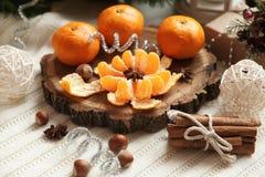 Tangerinen und Zimt auf dem Tisch nahe dem Weihnachtsbaum Lizenzfreies Stockbild