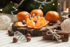 Tangerinen und Zimt auf dem Tisch nahe dem Weihnachtsbaum Stockfotos