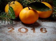 Tangerineniederlassungen 2016 und -nadeln des neuen Jahres auf grauem Hintergrund Stockbilder