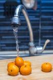 Tangerines διά την πίεση του νερού στο νεροχύτη κουζινών Στοκ Εικόνες