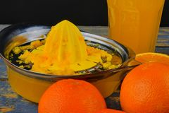 Tangerines, πορτοκάλια, ένα ποτήρι του χυμού από πορτοκάλι και χειρωνακτικά εσπεριδοειδή squezeer στο μπλε ξύλινο υπόβαθρο μισά π Στοκ Εικόνες