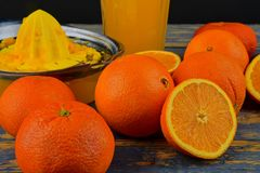 Tangerines, πορτοκάλια, ένα ποτήρι του χυμού από πορτοκάλι και χειρωνακτικά εσπεριδοειδή squezeer στο μπλε ξύλινο υπόβαθρο μισά π Στοκ Φωτογραφία