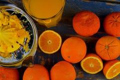 Tangerines, πορτοκάλια, ένα ποτήρι του χυμού από πορτοκάλι και χειρωνακτικά εσπεριδοειδή squezeer στο μπλε ξύλινο υπόβαθρο μισά π Στοκ εικόνες με δικαίωμα ελεύθερης χρήσης