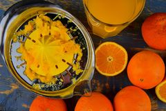 Tangerines, πορτοκάλια, ένα ποτήρι του χυμού από πορτοκάλι και χειρωνακτικά εσπεριδοειδή squezeer στο μπλε ξύλινο υπόβαθρο μισά π Στοκ εικόνα με δικαίωμα ελεύθερης χρήσης