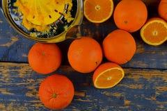 Tangerines, πορτοκάλια, ένα ποτήρι του χυμού από πορτοκάλι και χειρωνακτικά εσπεριδοειδή squezeer στο μπλε ξύλινο υπόβαθρο μισά π Στοκ φωτογραφία με δικαίωμα ελεύθερης χρήσης