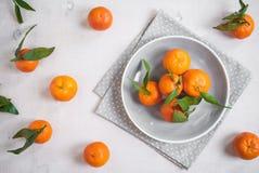 Tangerines στο άσπρο ξύλινο υπόβαθρο Γκρίζο ύφασμα σημείων Πόλκα Στοκ φωτογραφίες με δικαίωμα ελεύθερης χρήσης
