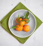 Tangerines στο άσπρο ξύλινο υπόβαθρο και το πράσινο ύφασμα Στοκ Εικόνα