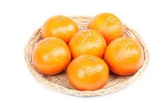 Tangerines в плетеной плите на белой предпосылке Стоковая Фотография