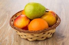 Tangerines, груши и нектарины в плетеной корзине на таблице Стоковые Фото