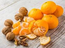 Tangerines и грецкие орехи на таблице стоковые изображения rf