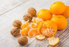 Tangerines и грецкие орехи на таблице стоковое фото rf