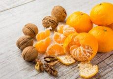 Tangerines и грецкие орехи на таблице стоковая фотография