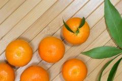 Tangerines и листья зеленого цвета на светлой предпосылке Стоковые Фото