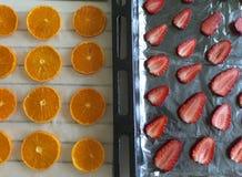 Tangerines и клубники отрезаны положенный вне на бумагу еды Для сушить и украшать десерты стоковые фотографии rf