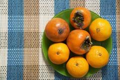 Tangerines и хурмы в зеленой плите на таблице Стоковые Изображения RF