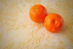 2 tangerines на предпосылке текстурированных поверхностей Стоковые Изображения
