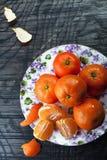 Tangerines на плите на темной предпосылке Стоковые Изображения