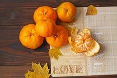 Tangerines с желтыми листьями на деревянной предпосылке стоковая фотография