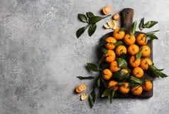 Tangerines с зелеными листьями на деревянной доске на светлой предпосылке Стоковые Фотографии RF
