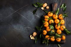 Tangerines с зелеными листьями на деревянной доске на темной предпосылке Стоковое Изображение
