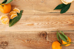 Tangerines с зелеными листьями на деревянной предпосылке стоковые изображения rf
