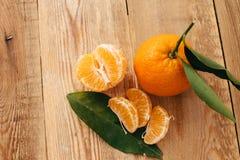 Tangerines с зелеными листьями на деревянной предпосылке стоковая фотография