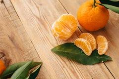 Tangerines с зелеными листьями на деревянной предпосылке стоковое изображение rf