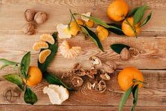 Tangerines с зелеными листьями на деревянной предпосылке стоковое изображение