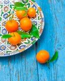 Tangerines с листьями в плите на деревянной предпосылке, в сини Стоковые Изображения RF