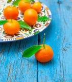 Tangerines с листьями в плите на деревянной предпосылке, в сини Стоковая Фотография RF