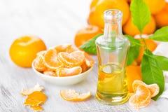 Tangerines с листьями и бутылкой необходимого цитруса смазывают на белой предпосылке Стоковые Фотографии RF