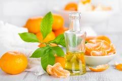 Tangerines с листьями и бутылкой необходимого цитруса смазывают на белой предпосылке Стоковое Изображение