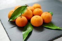Tangerines с листьями на доске шифера Стоковое Фото