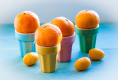 Tangerines. In the colorful cups Royalty Free Stock Images