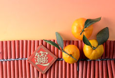 Tangerines and auspicious ornament on firecrackers Royalty Free Stock Photos
