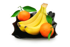 Tangerines and banana in a plate Stock Photos