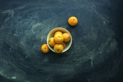 Tangerines in bowl on dark background. Super food. Tropical local product of Thailand and China. Top view flat lay stock images