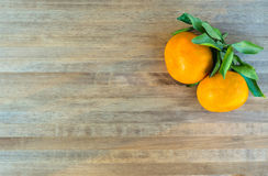 Tangerines bright orange snow. Rntangerines with green leaves on a wooden background snow Stock Image