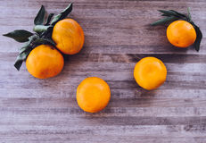 Tangerines bright orange snow. Rntangerines with green leaves on a wooden background snow Royalty Free Stock Image