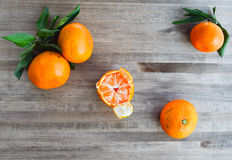 Tangerines bright orange snow. Rntangerines with green leaves on a wooden background snow Stock Photography
