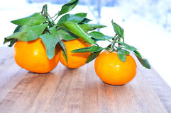 Tangerines bright orange snow. Rntangerines with green leaves on a wooden background snow Stock Photos