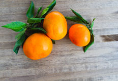 Tangerines bright orange snow. Rntangerines with green leaves on a wooden background snow Stock Photo