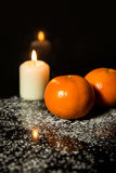 Tangerines and Candle on icing sugar, black stone and black back Stock Photography