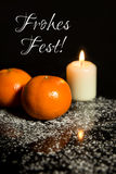 Tangerines and Candle on icing sugar, black stone and black back Royalty Free Stock Photography
